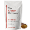 A packet of red Bali kratom powder, with some powder on a wooden vessel.